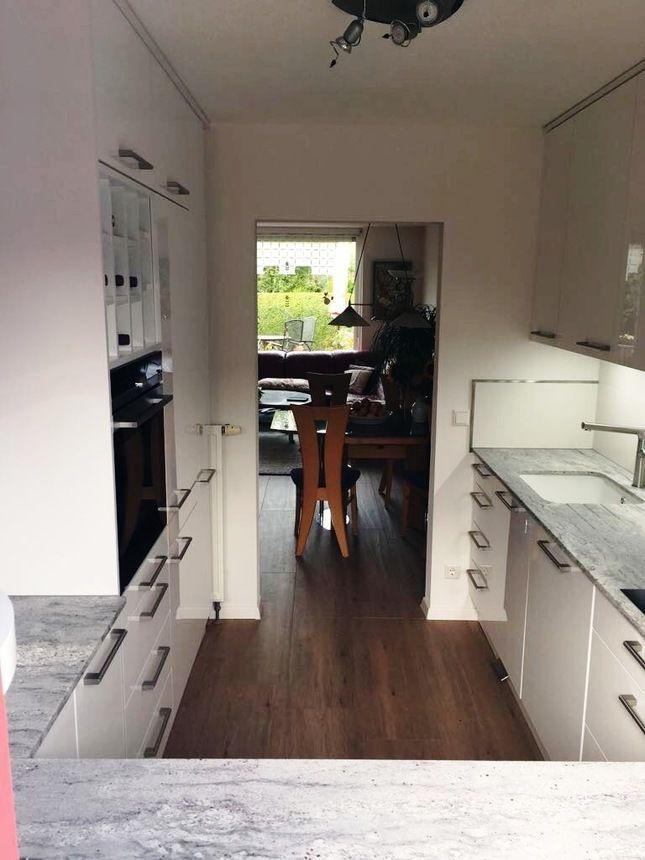 Diese küche geizt nicht mit arbeitsfläche und ablagemöglichkeiten selbst ein weinregal passt noch hinein das dekor in hochglanz weiß mit schwarzer